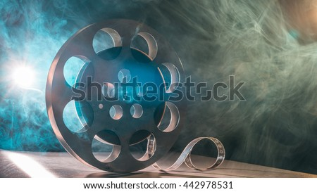 Movie reel of film in retro in the smoke of green and blueon a dark background - stock photo