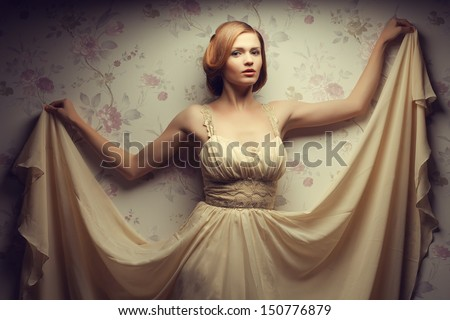 Movie star concept. Vintage portrait of a happy glamorous red-haired (ginger) girl posing in great flying beige dress and dancing. Retro (old Hollywood) style. Studio shot - stock photo