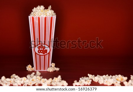 Movie theme popcorn box on red background - stock photo
