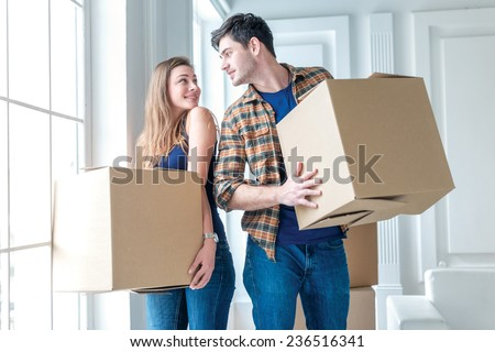 Moving a new family. A girl and a guy holding boxes for moving the hands and smiling at the camera while a couple in love standing at the window among the boxes in an empty apartment - stock photo