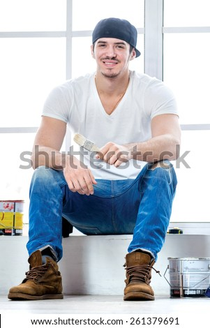 Moving and repairs in the apartment. Young painter man sitting on a windowsill and holding a brush in his hand while his friend standing in the background on a ladder in an empty apartment - stock photo