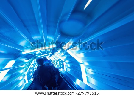 Moving blurred picture of escalator inside a tunnel. - stock photo