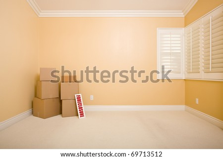 Moving Boxes and Foreclosure Real Estate Sign on Floor in Empty Room with Copy Space on Blank Wall. - stock photo
