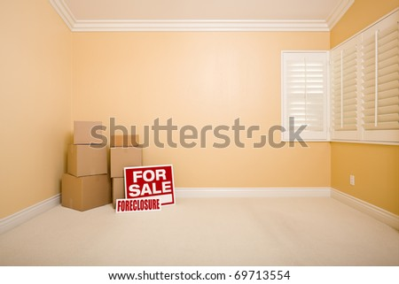 Moving Boxes, For Sale and Foreclosure Real Estate Signs on Floor in Empty Room with Copy Space on Blank Wall. - stock photo