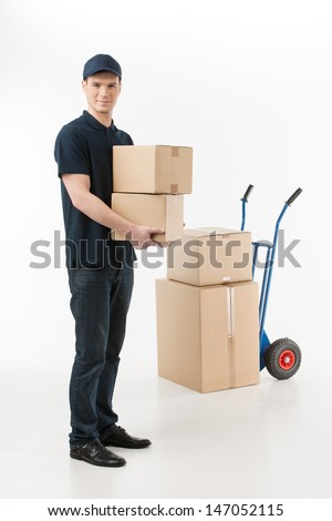 Moving boxes. Full length of young deliveryman holding a stack of boxes with a hand truck on the background - stock photo
