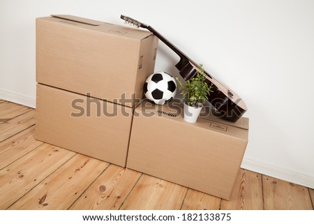 moving boxes, guitar and football in room - stock photo