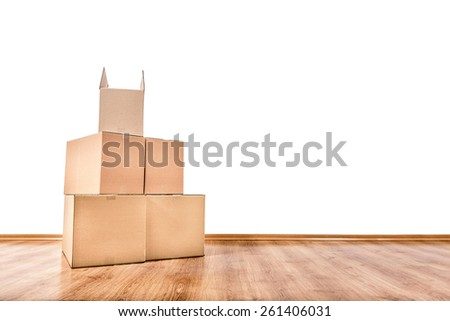 Moving boxes on the floor of an empty room with a white wall. - stock photo