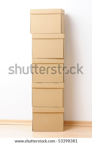 Moving boxes stacked in front of the wall - stock photo