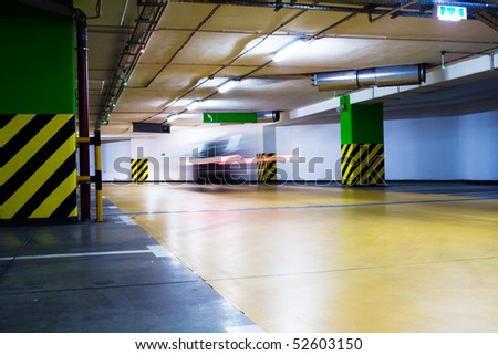 Moving car in underground parking garage, blurred motion. Neon light in bright industrial building. - stock photo