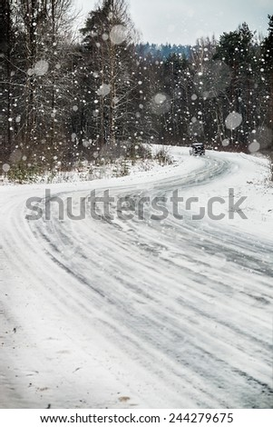 moving car on a forest road in the snow - stock photo