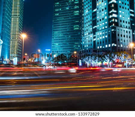 moving car with blur light through modern city at night. - stock photo