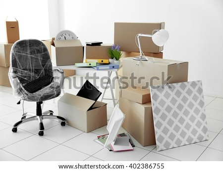 Moving cardboard boxes and personal belongings in empty office space - stock photo