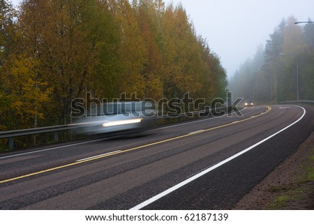 Moving cars on foggy weather in country road - stock photo