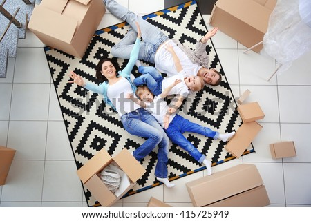 Moving concept. Happy family lying on carpet among cardboard boxes, top view - stock photo