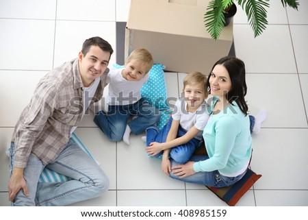 Moving concept. Happy family sitting on floor in new house with cardboard box, top view - stock photo
