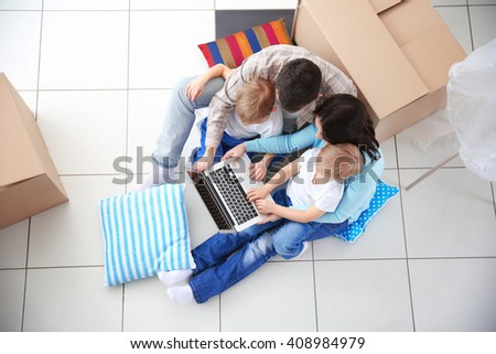 Moving concept. Happy family sitting on floor with laptop and cardboard box, top view - stock photo