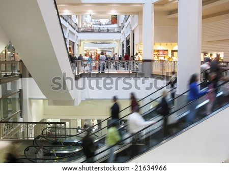 Moving crowd on escalator in shopping mall