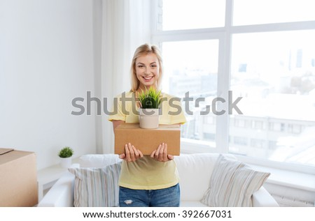 moving, delivery, accommodation and people concept - smiling young woman with cardboard box at home - stock photo