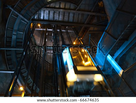 Moving elevator inside shaft with staircase. - stock photo