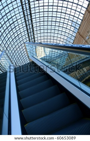 Moving escalator in office center - stock photo