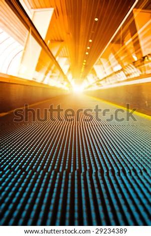 Moving escalator with bright light at the end