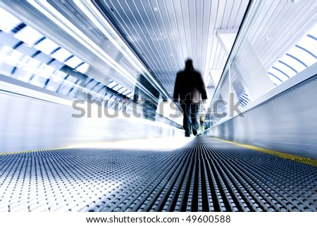 Moving escalator with person in airport - stock photo