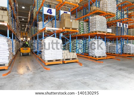 Moving forklift in warehouse between shelves - stock photo