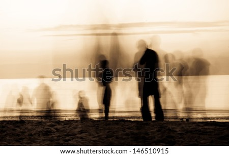 moving ghosts on the beach People walking on the beach at sunset. The movement blur makes it spooky. Duo tone - stock photo