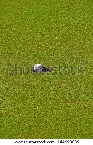 Moving golf ball about to drop in hole.