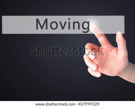 Moving - Hand pressing a button on blurred background concept . Business, technology, internet concept. Stock Photo