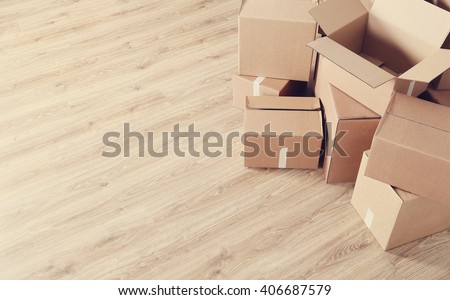 Moving home. Cardboard boxes on the floor - stock photo