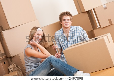 Moving house: Happy couple celebrating with glass of champagne new home