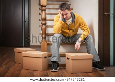 Moving house. Young man with cardboard boxes on a stairs.