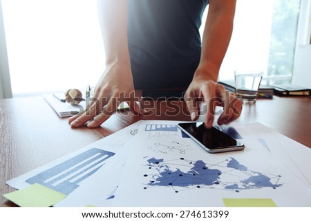 Moving Image of Business creative designer working wooden texture globe with smart phone on business document in office desk as internet concept - stock photo