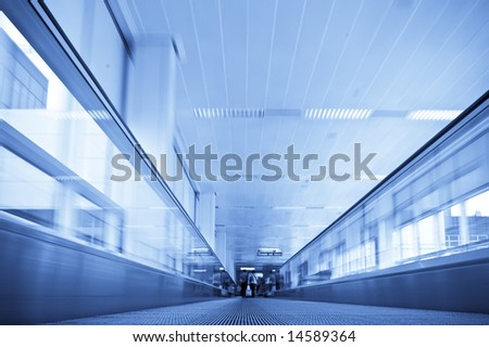 Moving in walkway along blue corridor. - stock photo