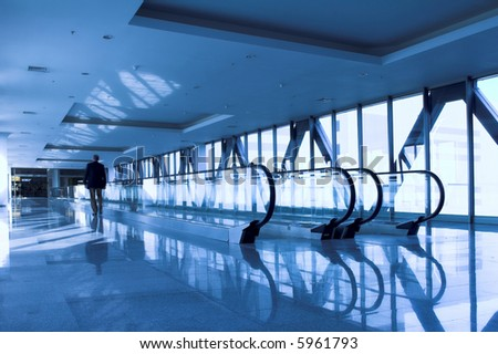 moving man near the escalator in the office hall - stock photo