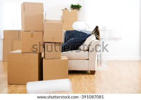 Moving: Man Takes a Break On Couch From Packing - stock photo