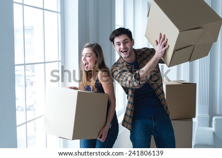 Moving new flat with fun and excitement. Young and beautiful couple is moving to new apartment surrounded with plenty of cardboard boxes. Both are smiling - stock photo