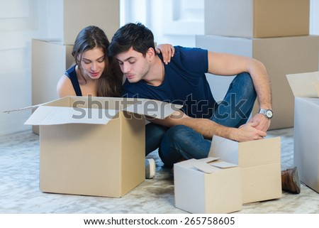 Moving new flat with fun and excitement. Young and beautiful couple is moving to new apartment surrounded with plenty of  boxes. Both are looking inside a box and thinking about future new cozy house - stock photo