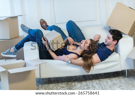 Moving new flat with fun and excitement. Young and beautiful couple is moving to new apartment surrounded with plenty of cardboard boxes. Both are laying on the sofa and dreaming about new cozy house - stock photo