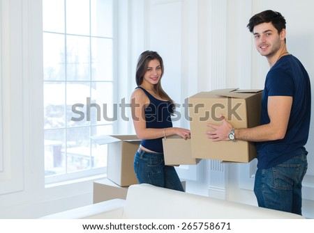 Moving new flat with fun and excitement. Young and beautiful couple is moving to new apartment surrounded with plenty of  boxes. Both are holding packs with their clothes while moving new apartment - stock photo