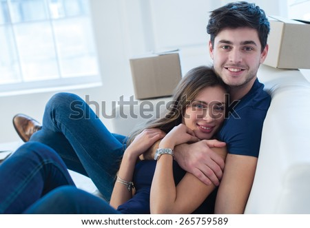 Moving new flat with fun and excitement. Young and beautiful couple is moving to new apartment surrounded with plenty of cardboard boxes. Both are sitting on the sofa and dreaming about new cozy home - stock photo