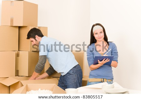 Moving new home young  happy couple unpacking cardboard boxes together