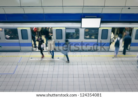 moving people enter carriage at a metro railway station with blank tv billboard, shot in Taipei, Taiwan, asia - stock photo