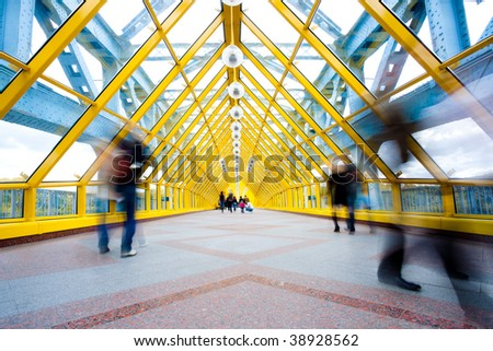 Moving people in modern yellow corridor - stock photo