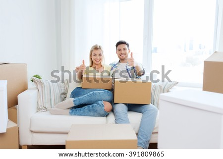 moving, people, repair and real estate concept - happy couple with big cardboard boxes showing thumbs up on sofa at new home - stock photo