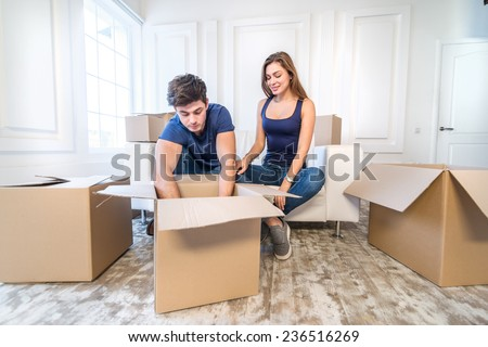 Moving, repairs, new flat. Couple in love get clothes from boxes for moving and wife hugging her husband while man and woman sitting on a sofa among boxes in an empty apartment - stock photo