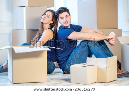 Moving, repairs, new home. A pair of a girl and a guy sitting back to back while man and woman sitting on the floor among the boxes in an empty apartment - stock photo