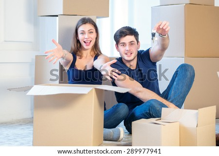 Moving, repairs, new keys to the apartment. Couple girl and the guy holding the keys to the apartment while man and woman sitting on the floor among the boxes in an empty apartment - stock photo