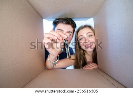 Moving, repairs, new keys to your new home. Smiling man and woman in love look into boxes for moving and get the key out of the box. View from inside the box. Close-up view of the keys - stock photo